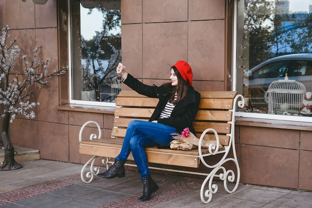 French woman in a red beret on a street bench