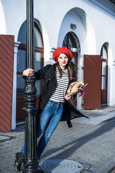 ベレットの通りにバゲットを持つフランス人女性