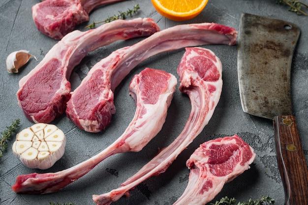 Набор сырых жирных бараньих отбивных с ингредиентами, морковью, апельсином, зеленью и старым мясным ножом, на сером каменном столе
