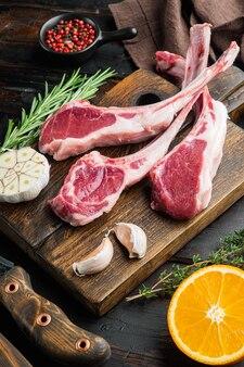 Набор сырых жирных бараньих отбивных с ингредиентами, морковью, апельсином, зеленью, на старом темном деревянном столе
