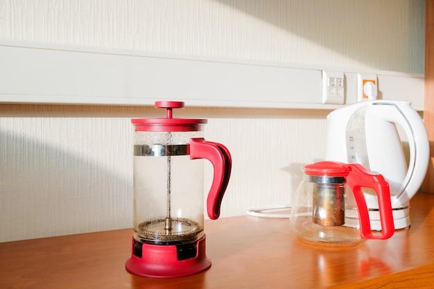 Стеклянный чайник frenchpress и электрический чайник на столе в свете солнца