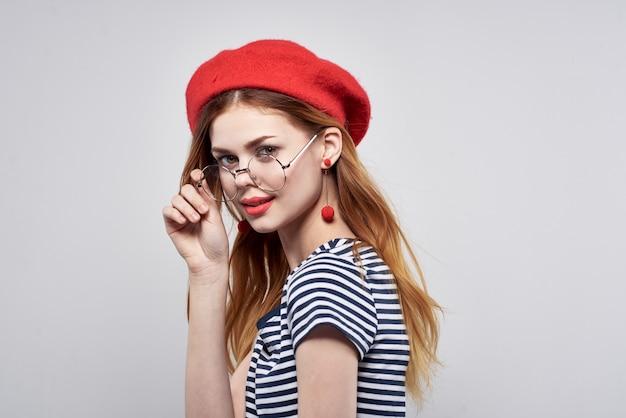 Француженка в полосатой футболке красными губами жестикулирует образ жизни рук. фото высокого качества