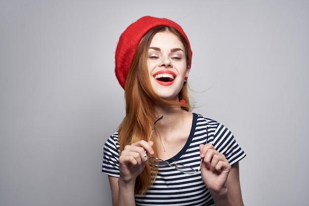 Француженка в полосатой футболке красными губами жестикулирует руками свежий воздух
