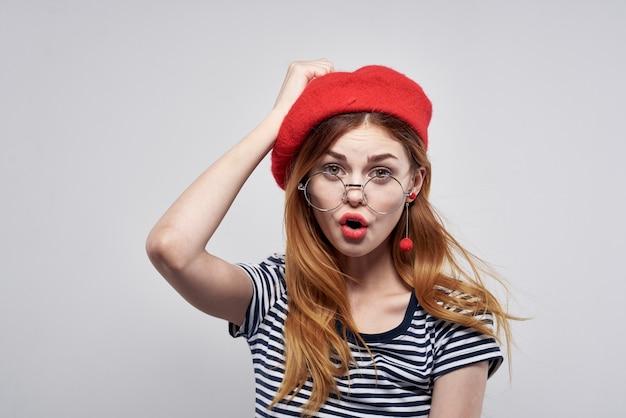 ファッションの魅力的な外観の赤いイヤリングジュエリーライフスタイルを提起する眼鏡をかけているフランス人女性