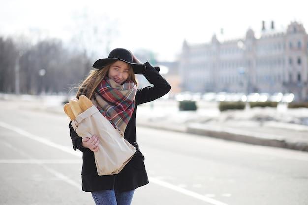 가게에서 나오는 길에 가방에 바게트를 넣은 프랑스 여성