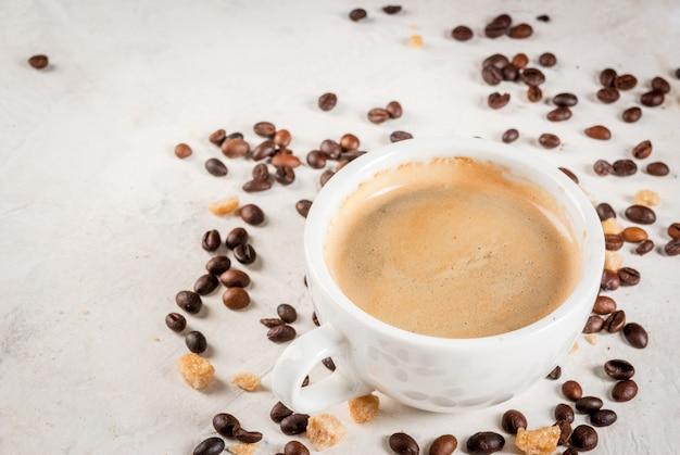 朝。食品の背景。コーヒーの粒、freshれたてのコーヒー1杯、白い石のテーブルの上に茶色の砂糖のスプーン。コピースペース