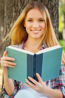 신선한 공기와 좋아하는 책. 공원에서 나무에 기대어 책을 들고 웃고 있는 아름다운 젊은 여성