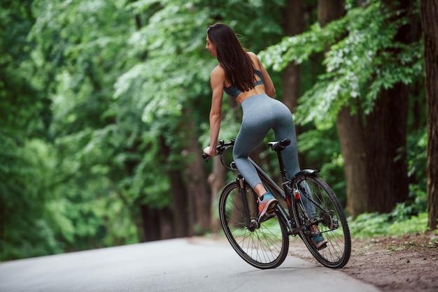 新鮮な空気。昼間の森の中のアスファルトの道路上の自転車の女性サイクリスト