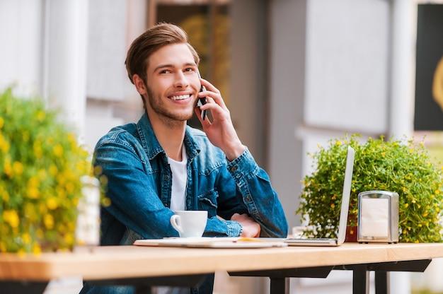 新鮮なアイデアのための新鮮な空気。携帯電話で話し、笑顔の陽気な青年