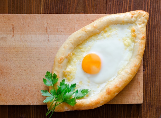 Fresh ajarian khachapuri with egg and cheese on a wooden plate, georgian cuisine