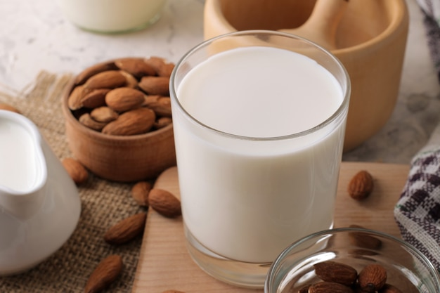 Fresh almond milk in a glass and almond nuts on a light background