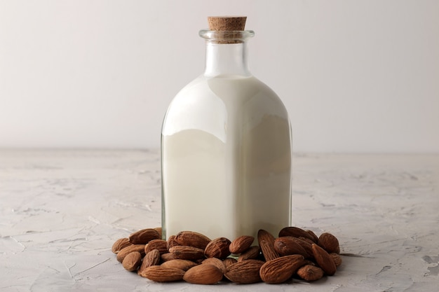 Fresh almond milk in a glass bottle and almond nuts on a light background