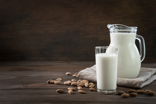 Fresh almond milk in glass and pitcher on dark wooden table background. rustic style.