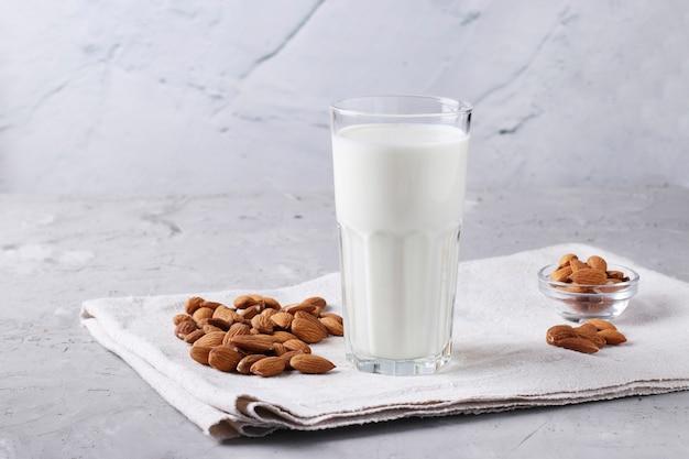透明なガラスの新鮮なアーモンドミルクと灰色のコンクリート表面のアーモンド、健康的なビーガンミルク代替品、水平フォーマット、クローズアップ