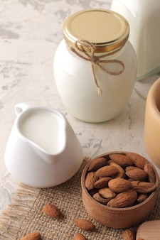 Fresh almond milk in a milk jug and almond nuts on a light background