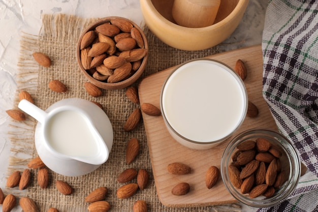 Fresh almond milk in milk jug and almond nuts. top view on a light background