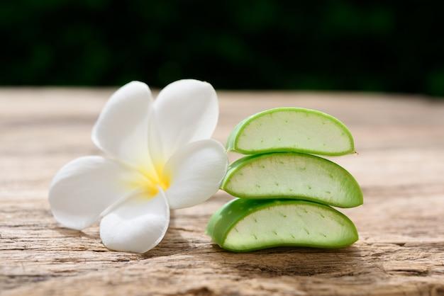 나무 테이블, 스파 치료 및 바디 스킨 케어 개념에 신선한 알로 베라와 plumeria 스파 꽃
