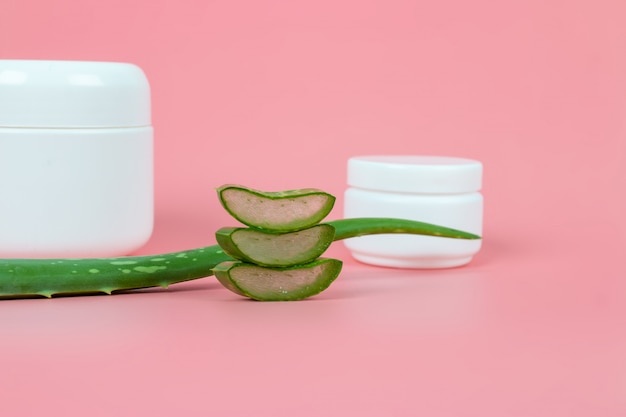 Fresh aloe vera leaves and slices on pastel pink background for health and beauty products.
