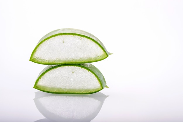 Fresh aloe vera slices on white surface with reflection