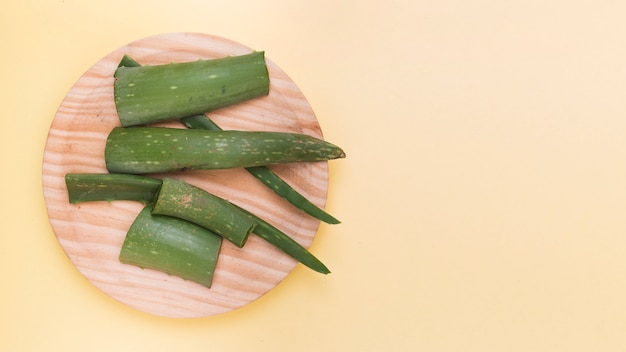 Fresh aloe vera slices on wooden plate against beige backdrop