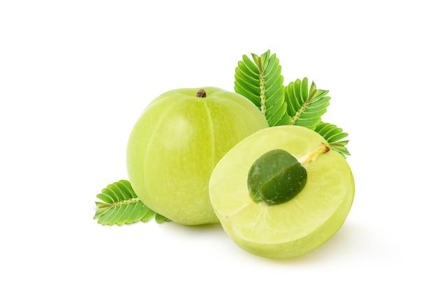 新鮮なアムラ(インディアングーズベリー)の果実を半分にカットし、葉を白で隔離します。