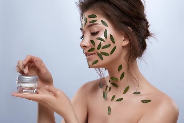 그녀의 손에 크림을 들고 몸에 녹색 잎을 가진 신선하고 아름다운 여성