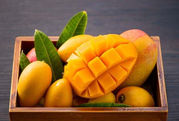 Свежие и красивые плоды манго в деревянной коробке с нарезанными кубиками кусками манго на темном деревянном фоне, пространство для копирования (пространство для текста), пробел для текста