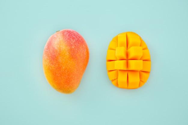 Свежие и красивые плоды манго с нарезанными кубиками кусками манго на светло-синем фоне, копией пространства (пространство для текста), пробелом для текста, видом сверху.