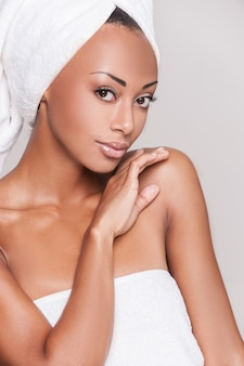 新鮮で美しい。あごに手をつないで、灰色の背景に立ってカメラを見ている美しい若いアフリカ系アメリカ人の上半身裸の女性の肖像画