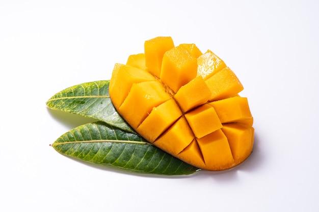 新鮮で美しいスライスしたさいの目に切ったマンゴーの塊と葉は白い背景で隔離、コピースペース(テキストスペース)、テキストは空白