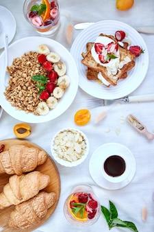 新鮮で明るいコンチネンタルブレックファーストテーブル、豊富な健康的な食事の種類。トップビュー、フラットレイアウト