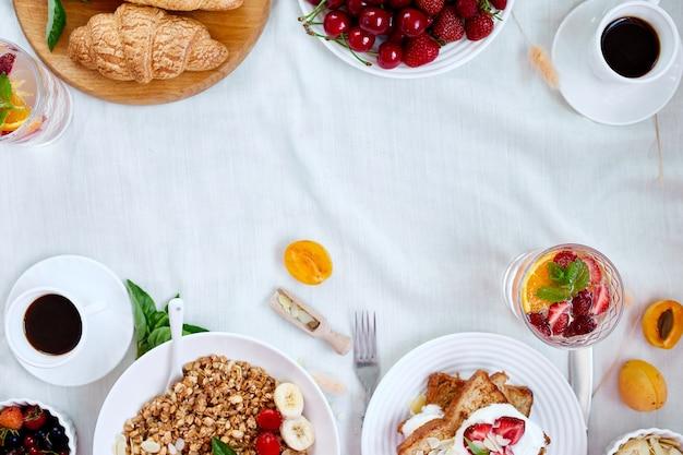 Свежий и яркий стол для континентального завтрака, обилие разнообразных здоровых блюд. вид сверху, плоская планировка