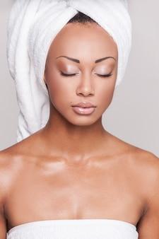 Свежий и чистый. красивая молодая афро-американская женщина без рубашки с закрытыми глазами, стоя на сером фоне