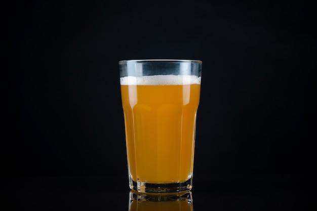 上に白い泡が付いた新鮮で冷たいガラスクラフトビール。