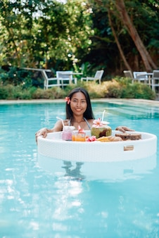 フローティングテーブルで新鮮でクールなアジア料理。日焼けした肌を持つ魅惑的で楽しいアジアの女性は、フローティングテーブルとプールで泳ぎ、カメラを見ます。