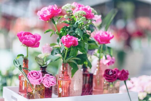Свежие и декоративные искусственные розы в разных вазах