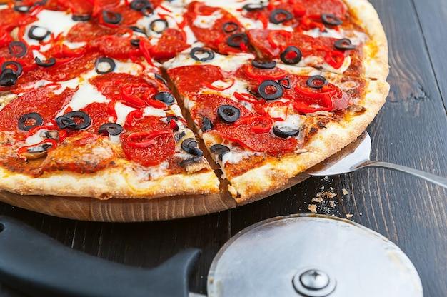 木製のテーブルとピザナイフで新鮮でおいしいイタリアンピザ