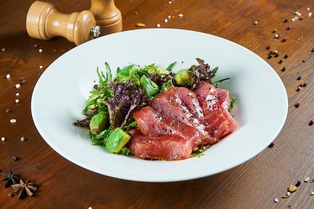 マグロ、レタス、アボカドのフレッシュでおいしいタタキサラダ。木製のテーブルの上の白いボウルで日本料理のおいしいシーフードサラダ。食べ物の写真を閉じる