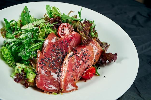 참치, 양상추, 아보카도와 신선하고 맛있는 타 타키 샐러드. 나무 테이블에 흰 그릇에 일본 요리의 맛있는 해산물 샐러드. 음식 사진을 닫습니다