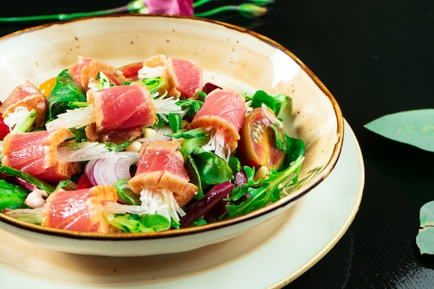 참치, 양상추, 붉은 양파, 체리 토마토, 무와 함께 신선하고 맛있는 타 타키 샐러드. 어두운 배경에 노란색 그릇에 일본 요리의 맛있는 해산물 샐러드.