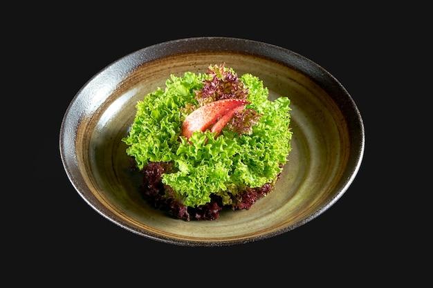 신선한 가재 샐러드가 그릇에 제공됩니다. 검정색 배경에 고립. 해물