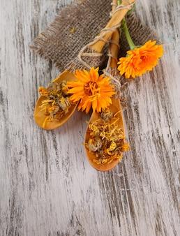 Свежие и сушеные цветы календулы на деревянном столе