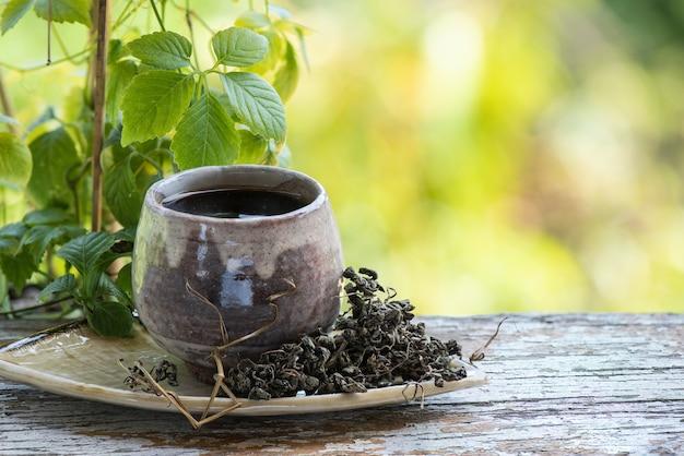 Свежие и сушеные gynostemma pentaphyllum или jiaogulan листья и чай на фоне природы боке.
