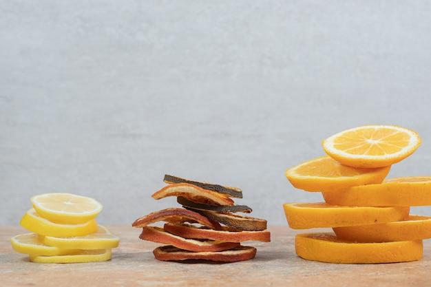 Свежие и сушеные дольки лимона и апельсина на мраморном столе. фото высокого качества