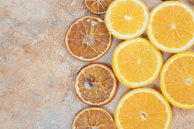 Свежие и сушеные дольки апельсина на мраморном фоне.