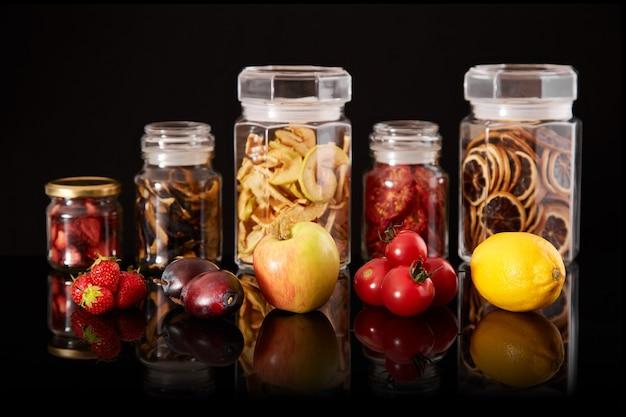 新鮮で乾燥した果物と野菜。瓶の中のドライフルーツの組成。