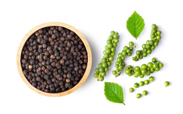 Свежий и сухой перец с листьями на белой стене