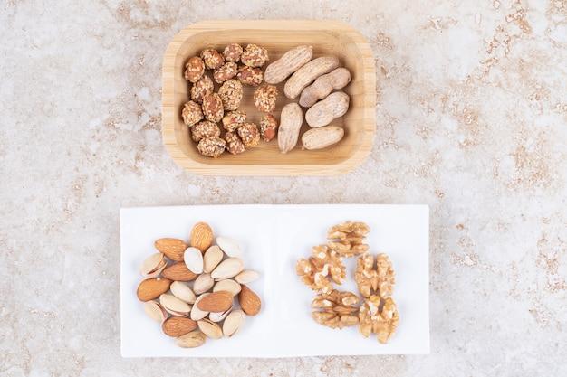 Свежий и глазированный арахис рядом с грецкими орехами, миндалем и фисташками