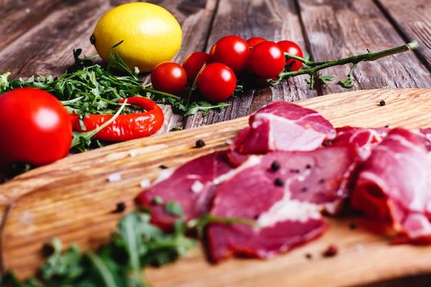 新鮮で健康的な食べ物。スライスした赤身の肉はルッコラと木製のテーブルの上にあります。