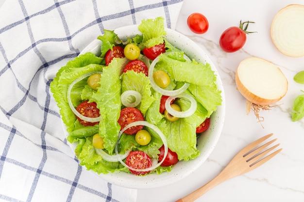 Свежий и полезный салат с листьями салата, луком, помидорами черри и оливками в миске. средиземноморская кухня